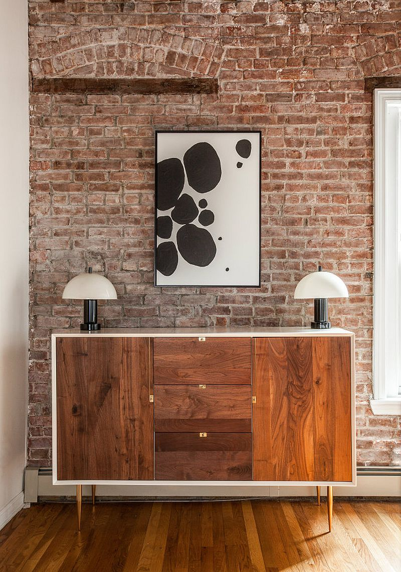 Lovely modern wooden buffet in the living and dining space with brick walls