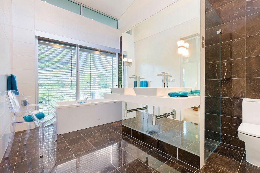 Super sleek contemporary bathroom with a white bathtub abd acrylic chair