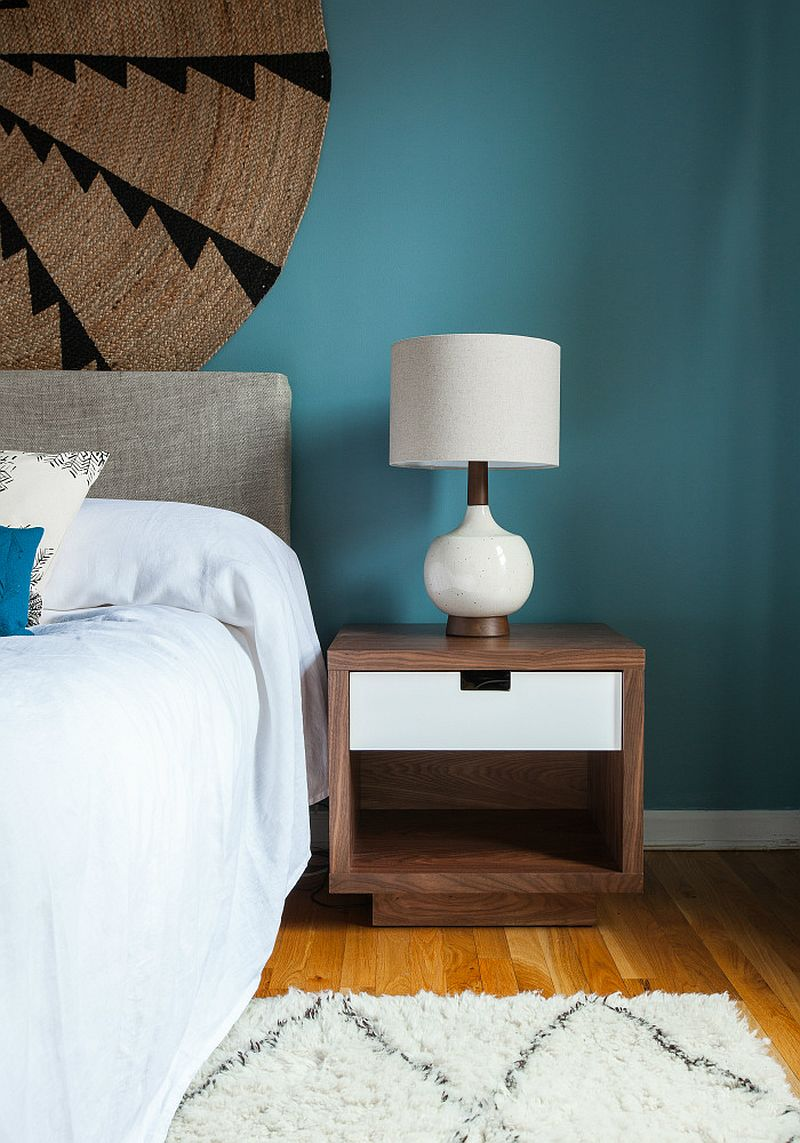 Walnut bedside table and table lamp give the contemporary bedroom a midcentury vibe