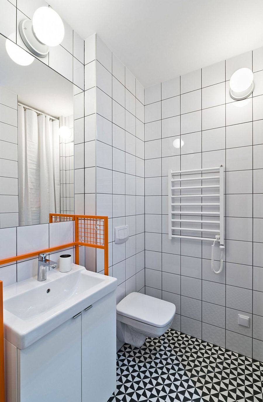 Black, white and gray shape a stylish, small bathroom inside the Poznan apartment