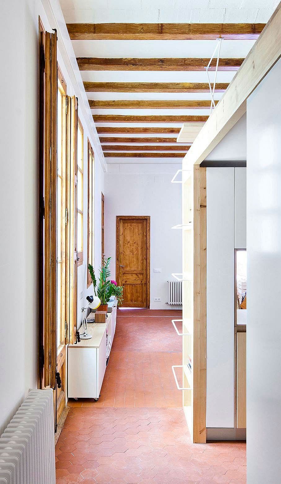 Large windows and exposed wooden beams showcase the past of the apartment