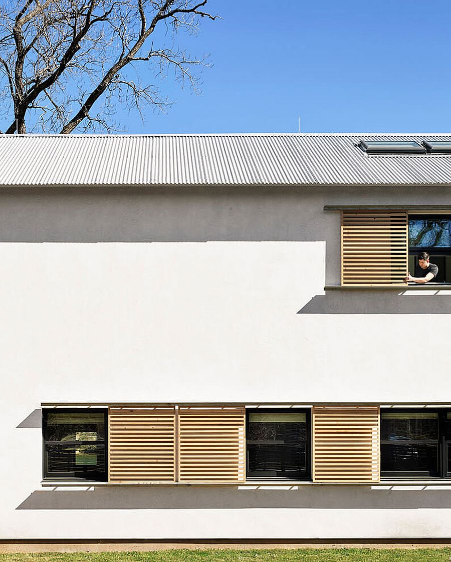 Series of windows covered with wooden slats give the exterior a unique look