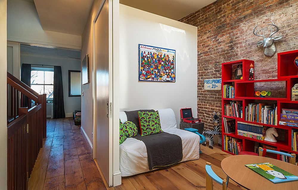 Contemporary kids' room with sofa bed and smart bookshelves in red [Design: Urban Pioneering Architecture]