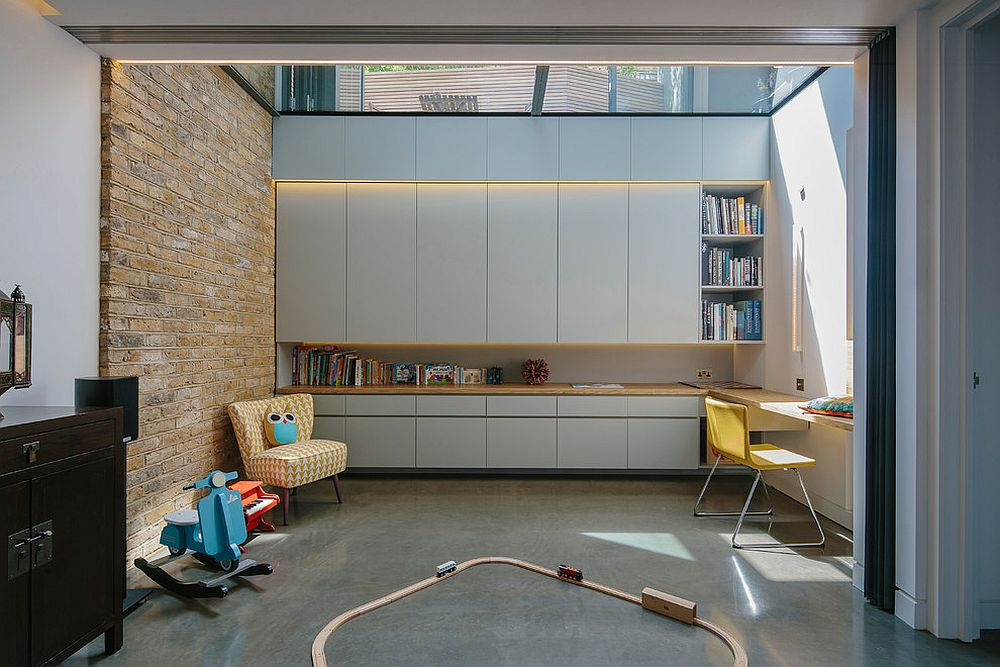 Playroom and kids study with skylight and feature brick wall [Design: Neil Dusheiko Architects]