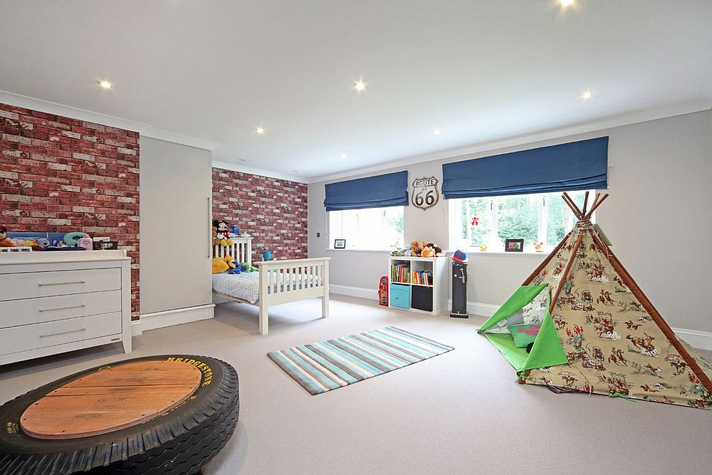 Spacious kids' bedroom with ample room for play area and exposed brick wall [Design: Noushka Design]