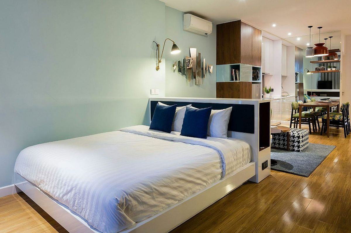Headboard wall separates the bedroom from the living space in a cool and breezy fashion