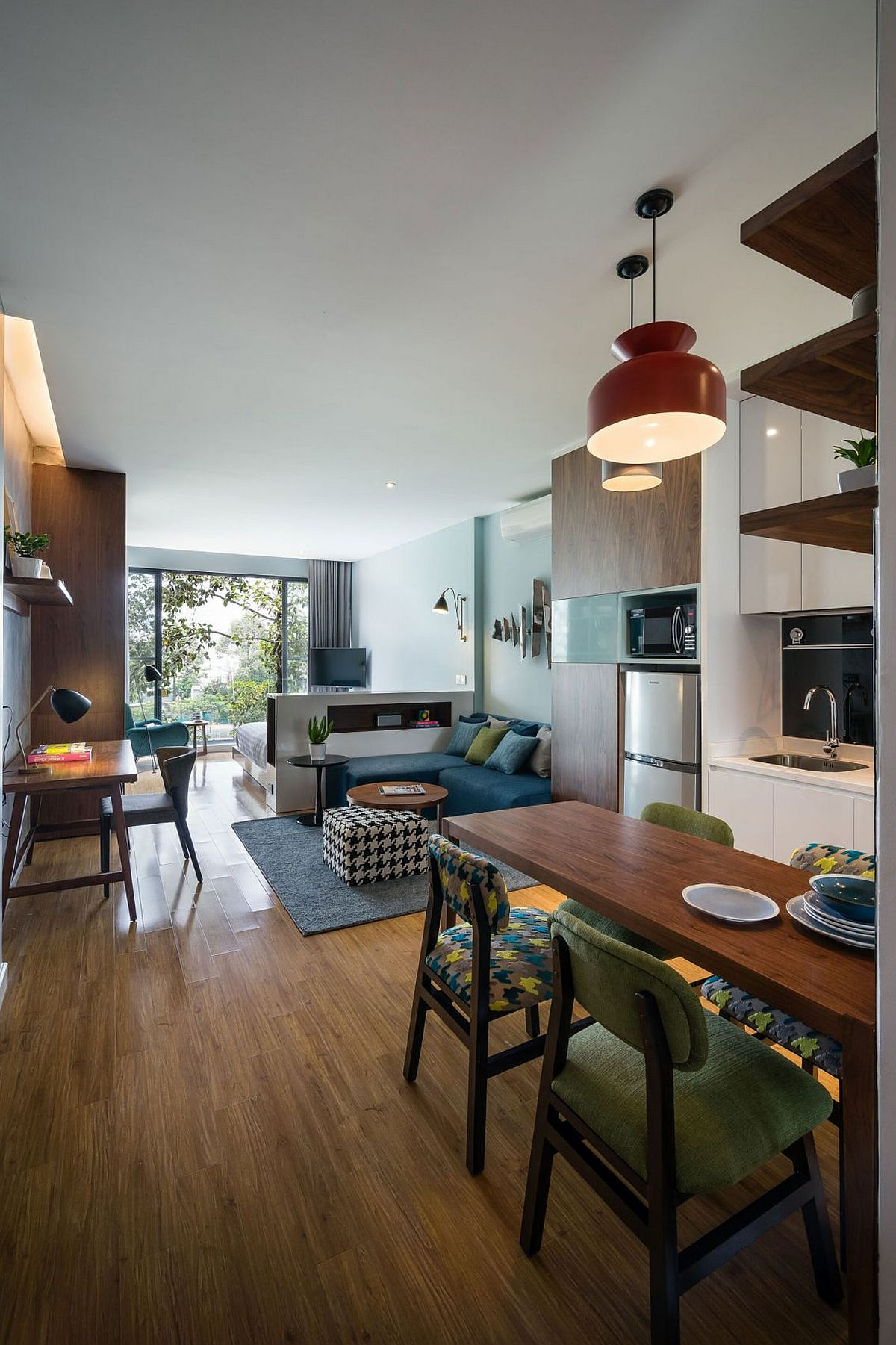 Open living area, kitchen and dining with a small sectional couch in blue and workdesk