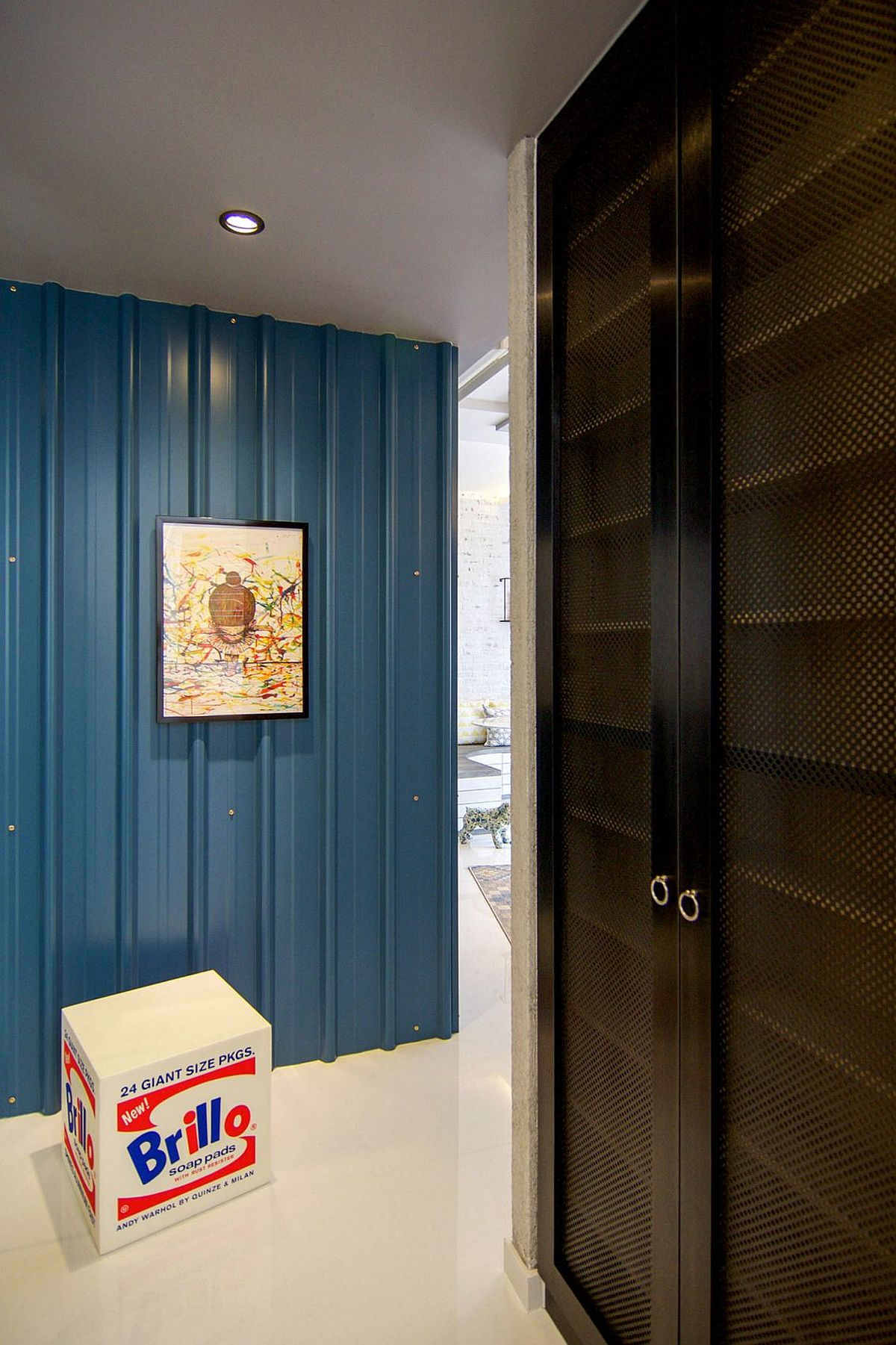 Blue metallic claddin on the wall welcomes you to the colorful home in Singapore