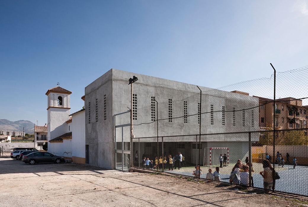 Tiny porthole windows punctuate the multipurpose hall at the Cerrillo de Maracena School in Granada.