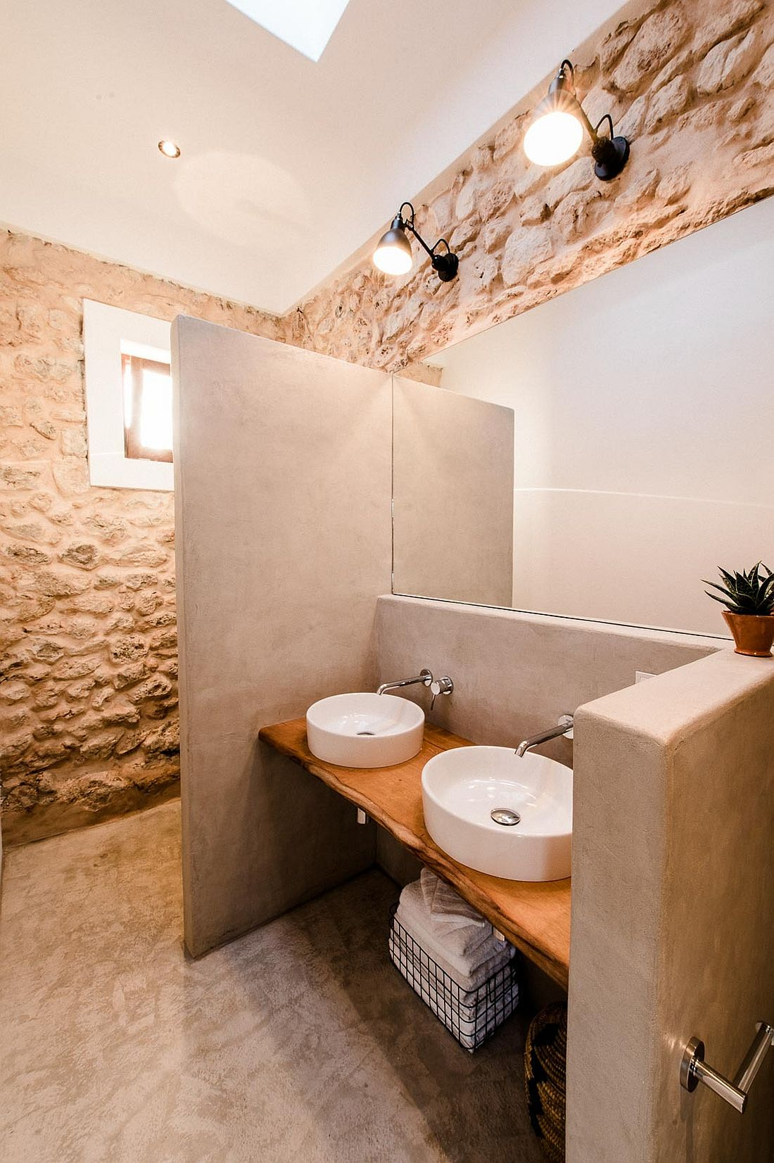 Classic stone walls coupled with modern aesthetics and live edge vanity in the bathroom