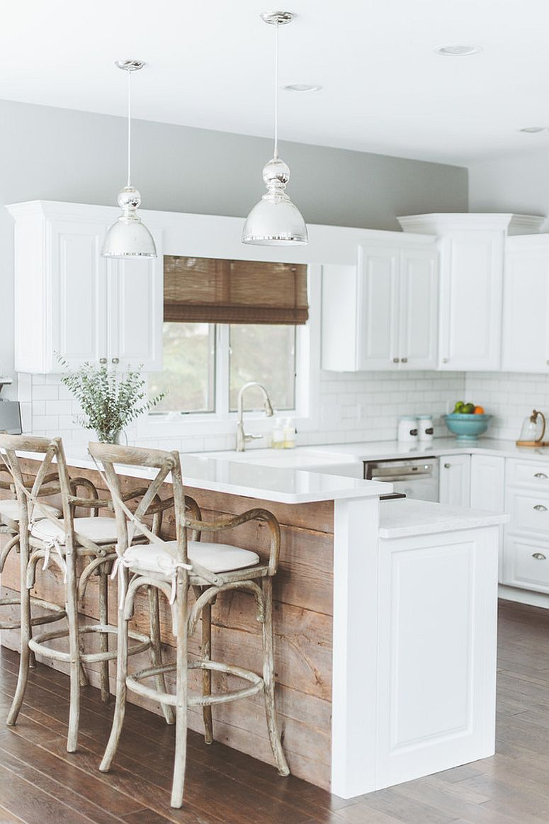Kitchen island covered in reclaimed wood brings contrast to the polished kitchen