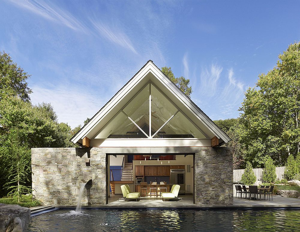 Contemporary pool house with glass garage door sits tight on the edge of the pool [Design: Randall Mars Architects]