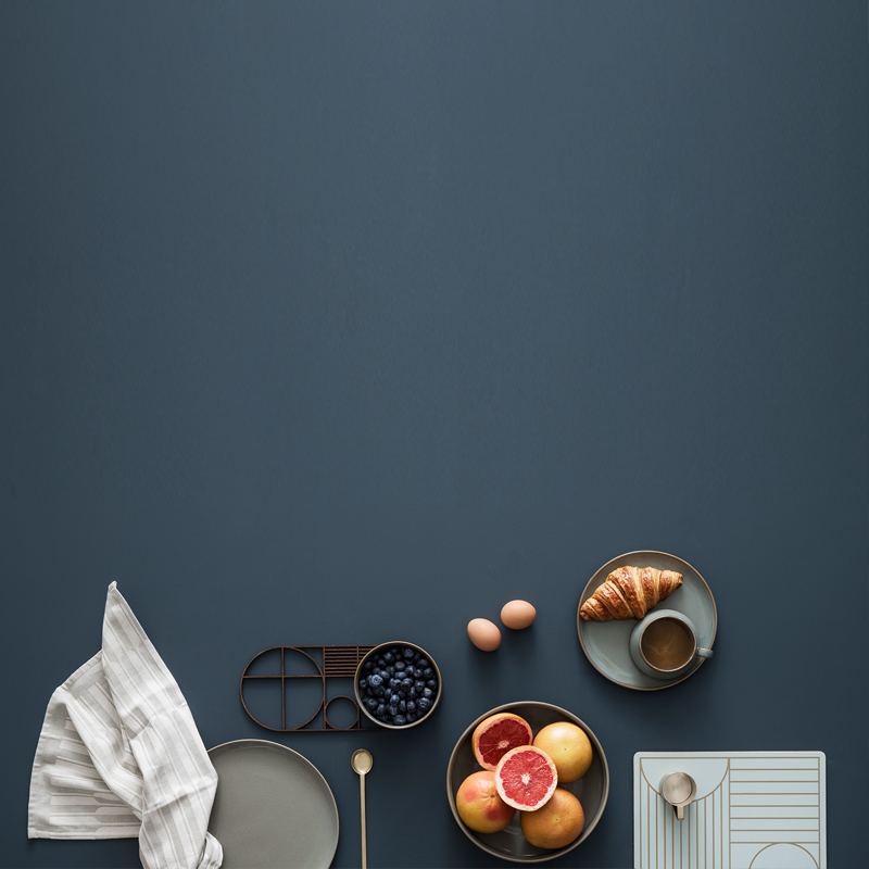 A rich grey backdrop highlights modern products by ferm LIVING