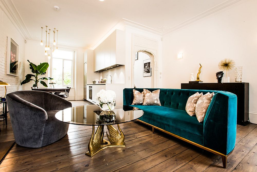 Classic midcentury living room with couch in velvety blue and gold [Design: Jino Design]