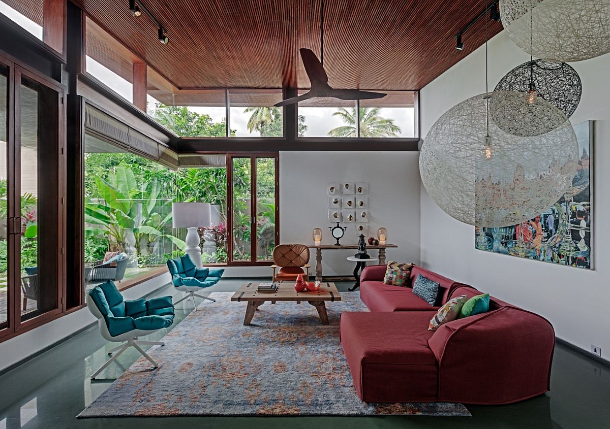 Living room with glass walls, colorful furniture and large pendants from Moooi