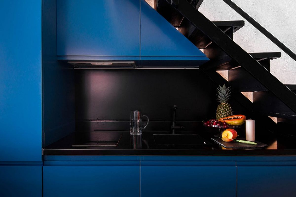 Smart modern kitchen station with cabinets in blue and a black countertop