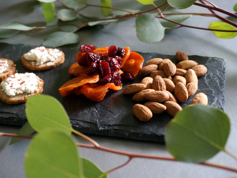 Eucalyptus leaves surround a cheese board (they should not be consumed)