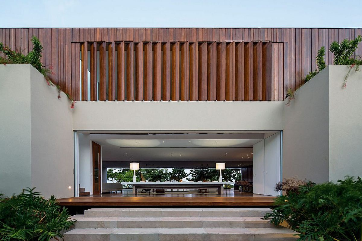 Wooden slats provide privacy and ventilation for the upper level of the contemporary home
