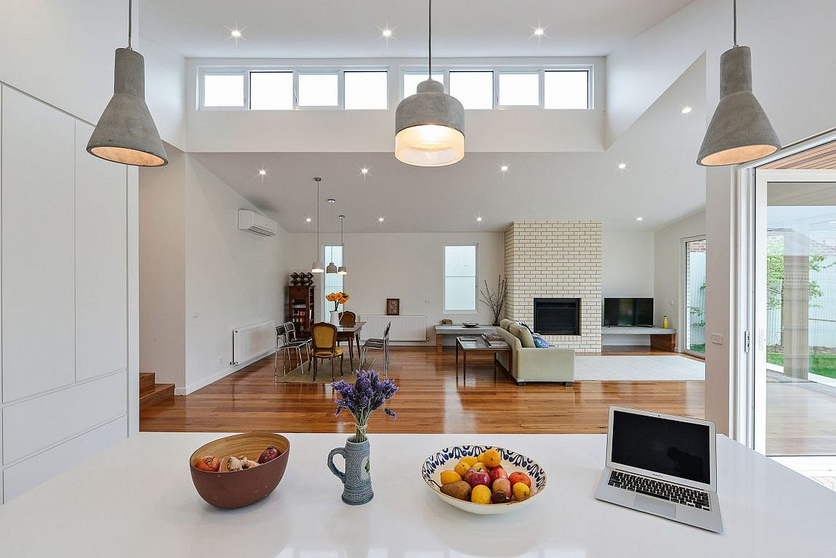 View of the living room and dining space from the contemporary kitchen in white