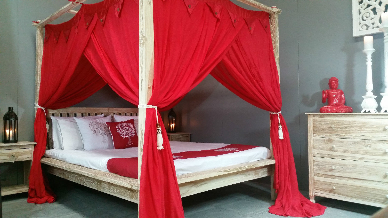 Boho bedroom with bright red canopy and wooden four poster bed