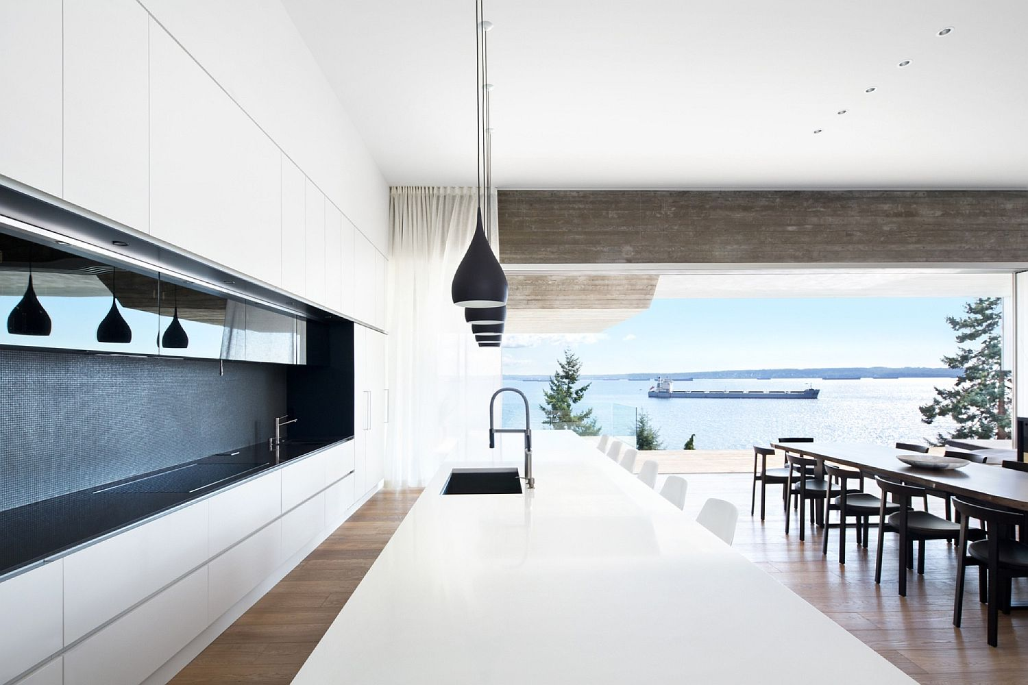Dashing minimal kitchen in whit with large island and black pendant lights