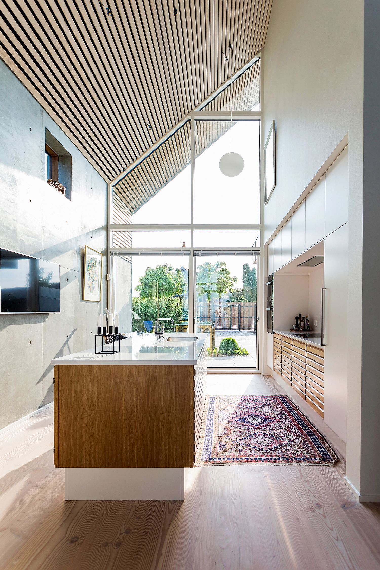 Angular roof, large glass windows and high ceilings give the interior an airy, modern appeal