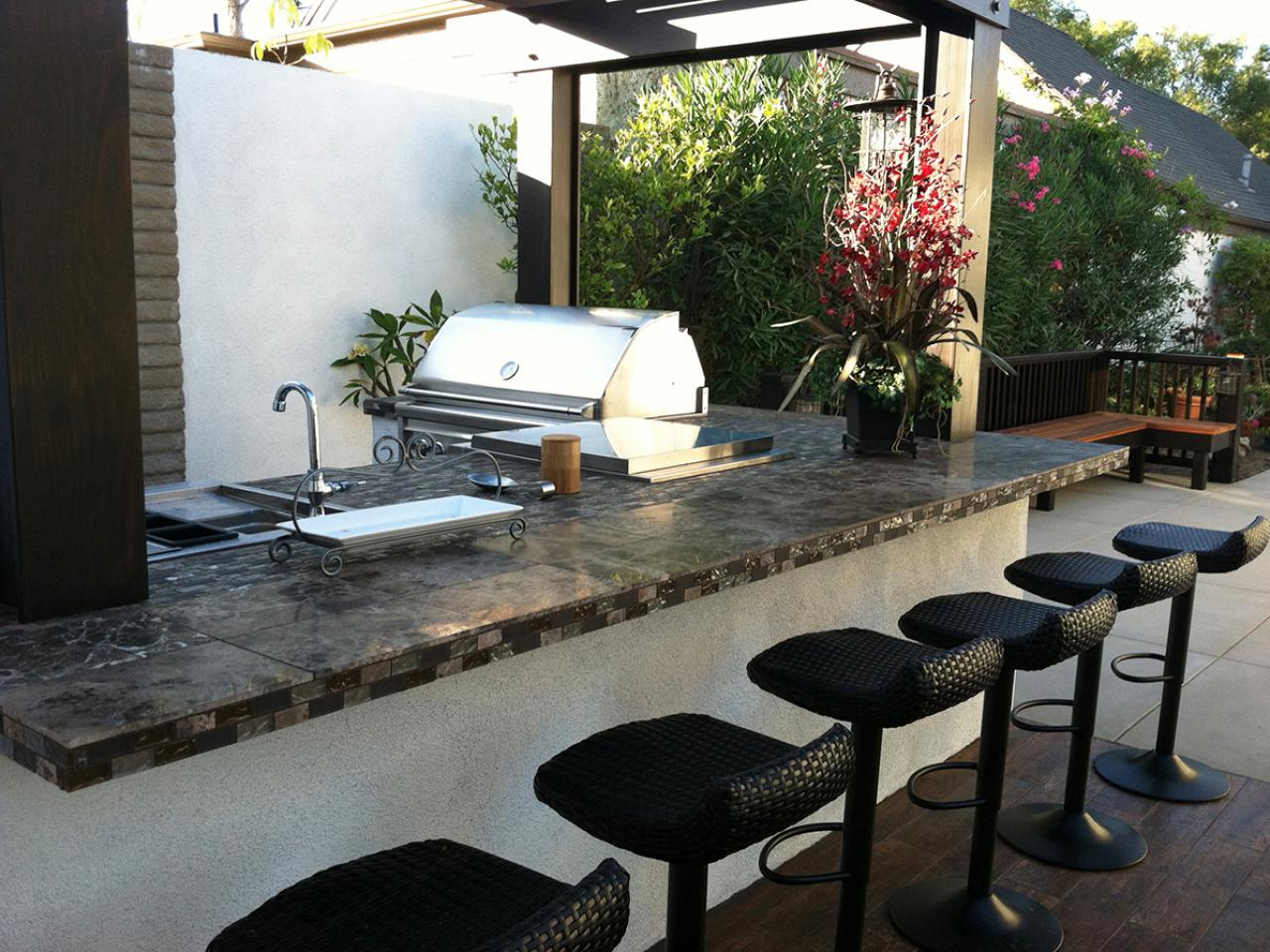 Bar-inspired outdoor kitchen with cute bar stools