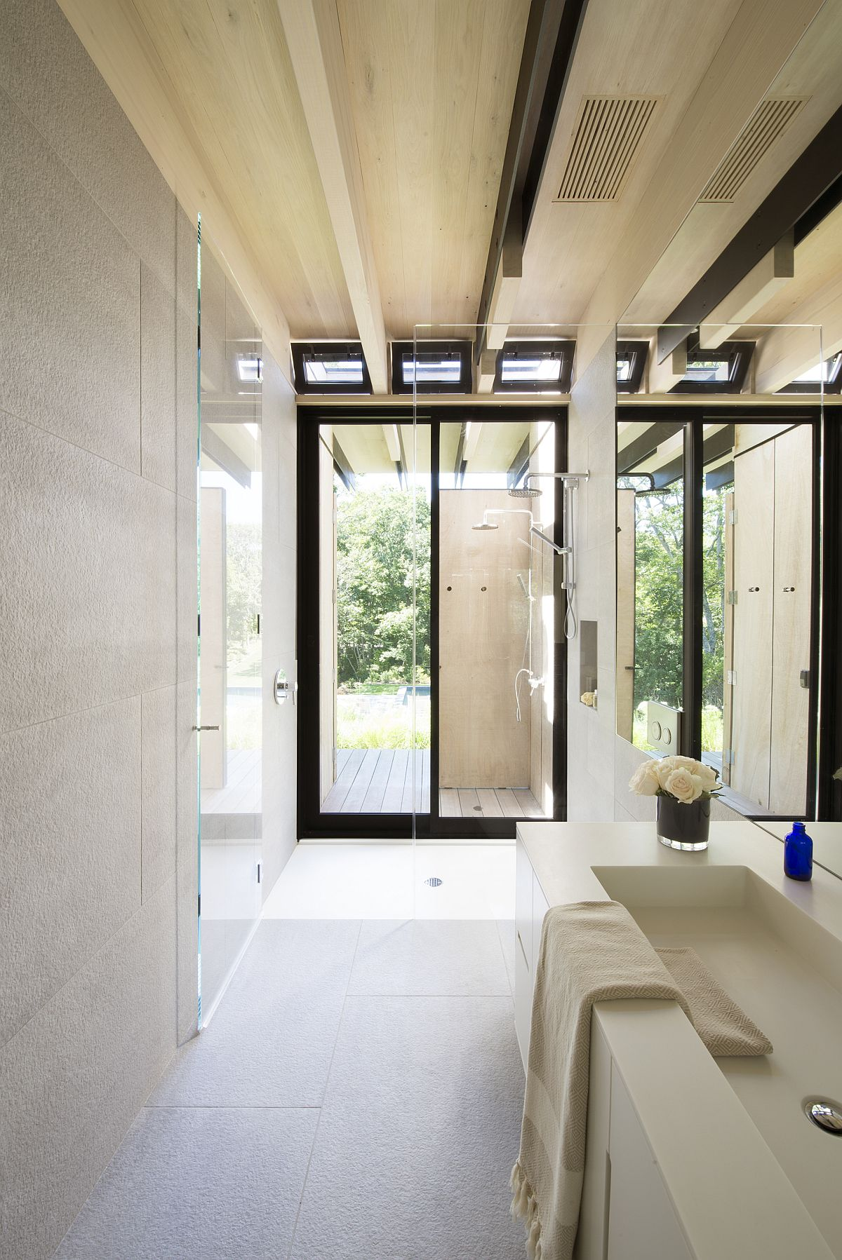 Contemporary bathroom in white with large windows and black window frames