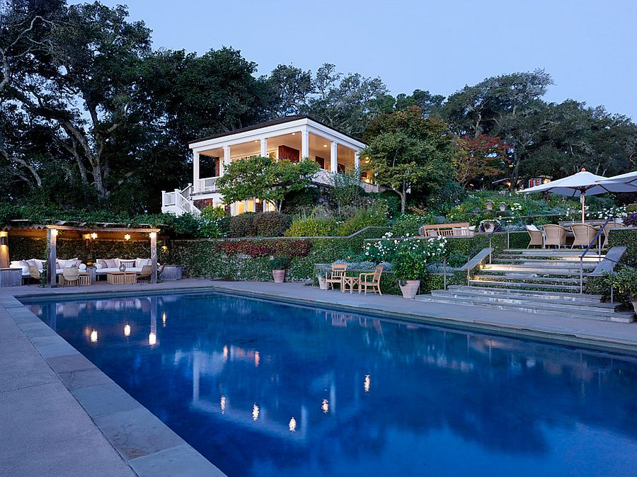 Pergola with gorgeous lighting and relaxing seating next to the pool
