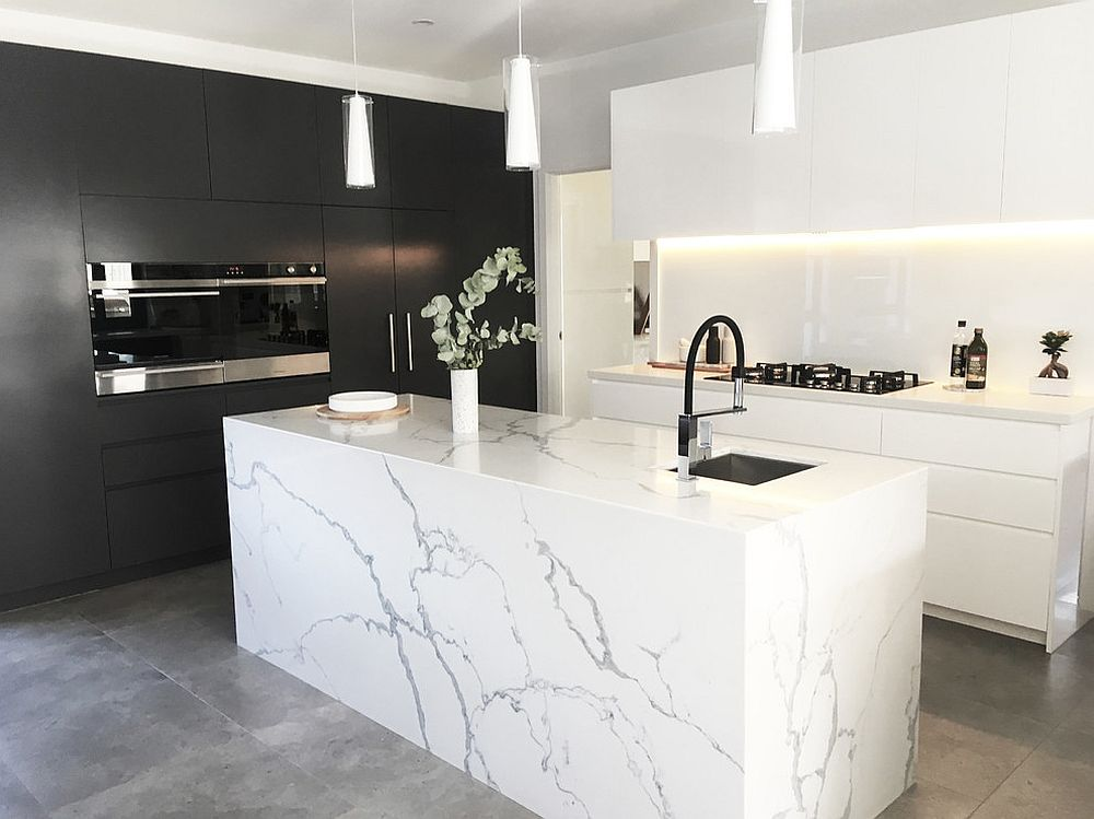 Modern kitchen in black and white with marble island and concrete floor