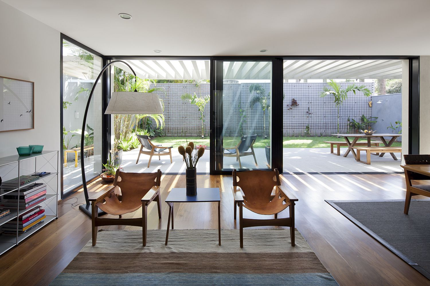 Dark framed glass doors connect the living area with the outdoor dining and backyard
