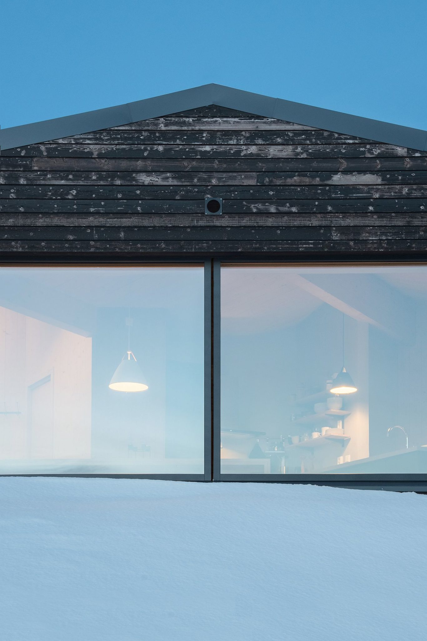 A look into the cabin from the snow-clad slopes around it