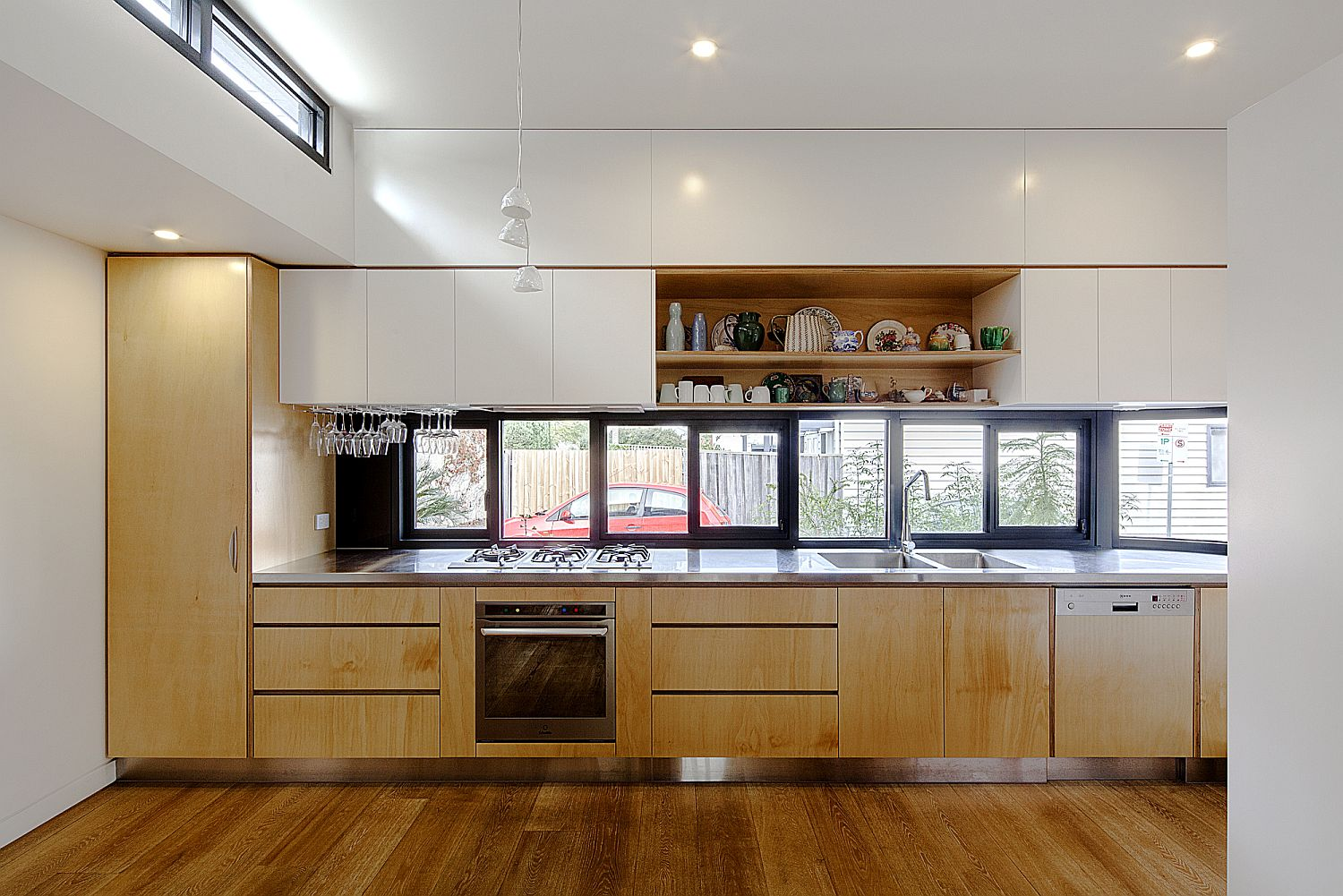 Wood and white modern kitchen with window above the kitchen counter