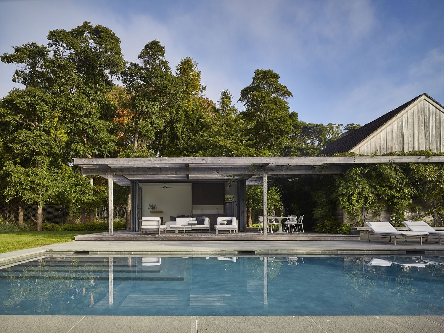 Elegant modern pool house with plenty of outdoor relaxation space