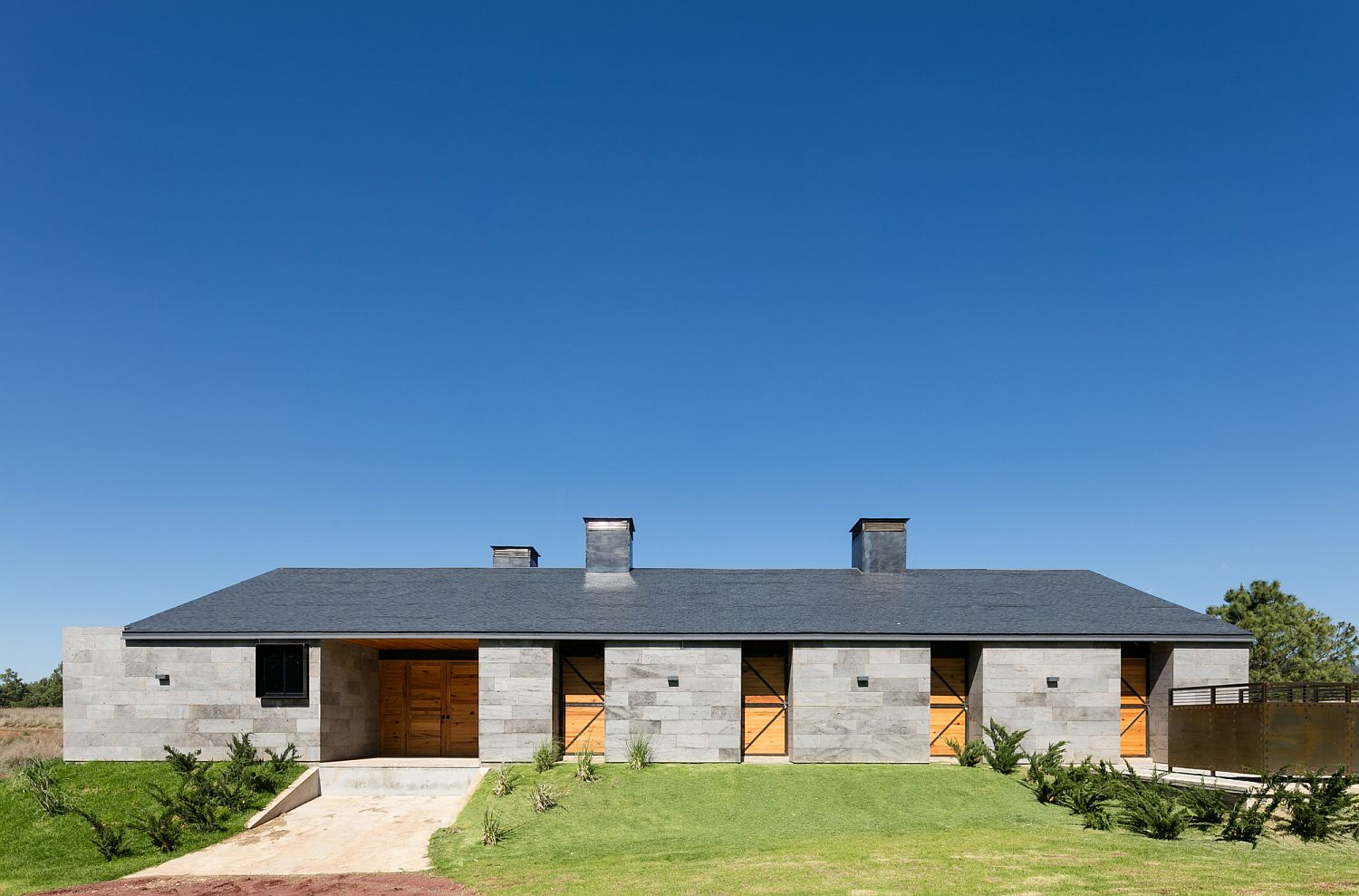 Modern Mexican ranch house with a gray exterior in volcanic rock
