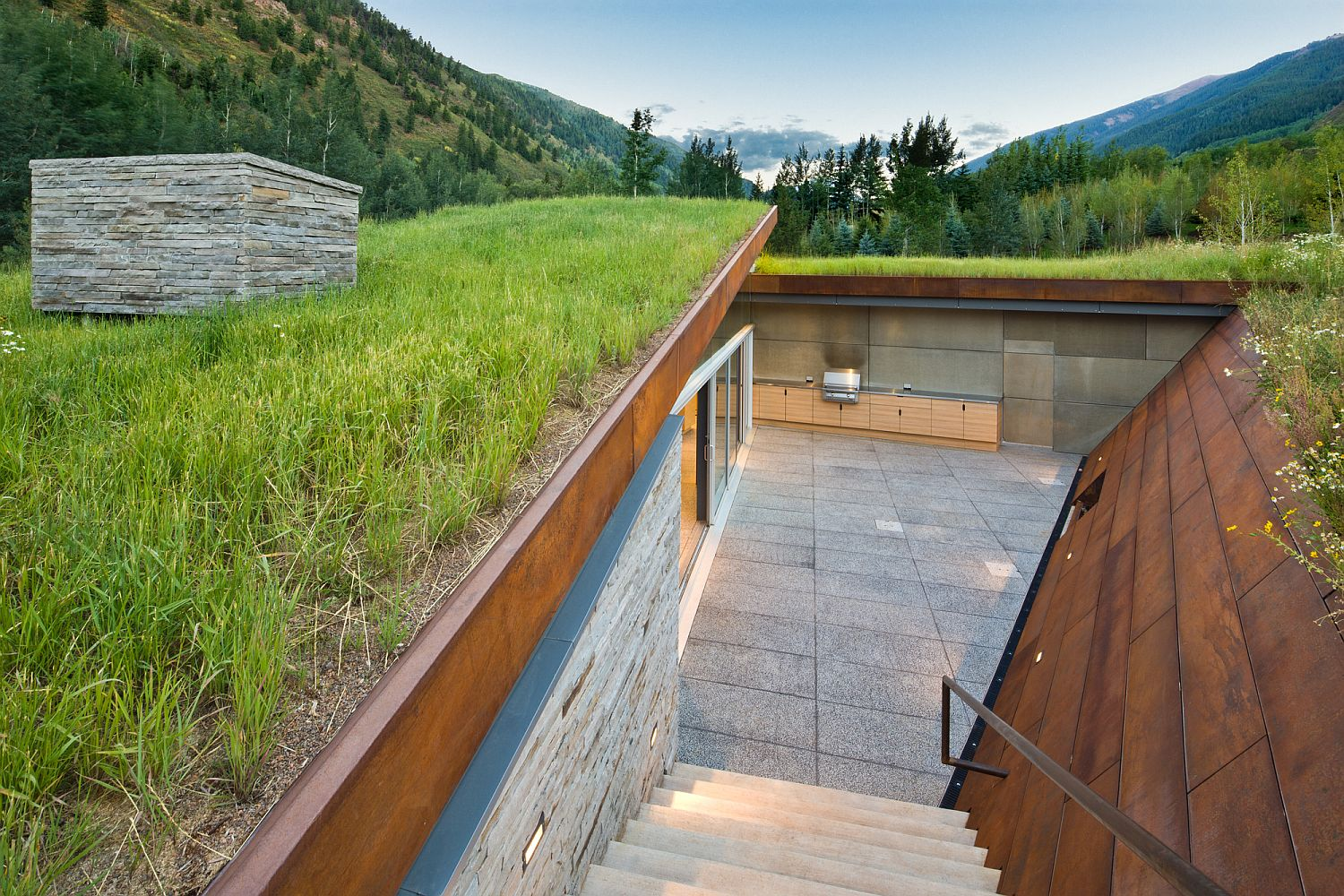 Private sunken outdoor space surrounded by corten clad walls