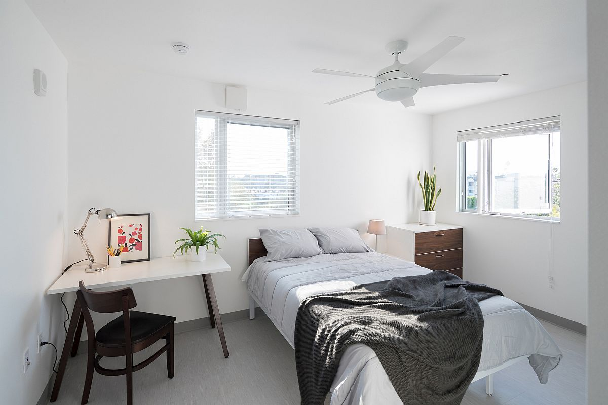 White bedroom inside the apartment unit with ample natural light