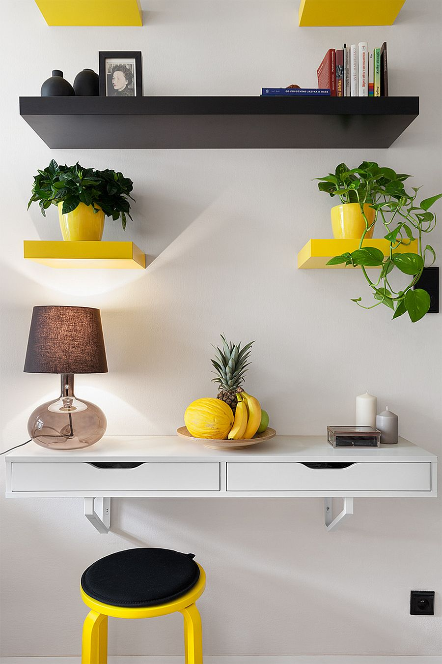 Yellow and black floating shelves act as plant holders inside this budget friendly apartment