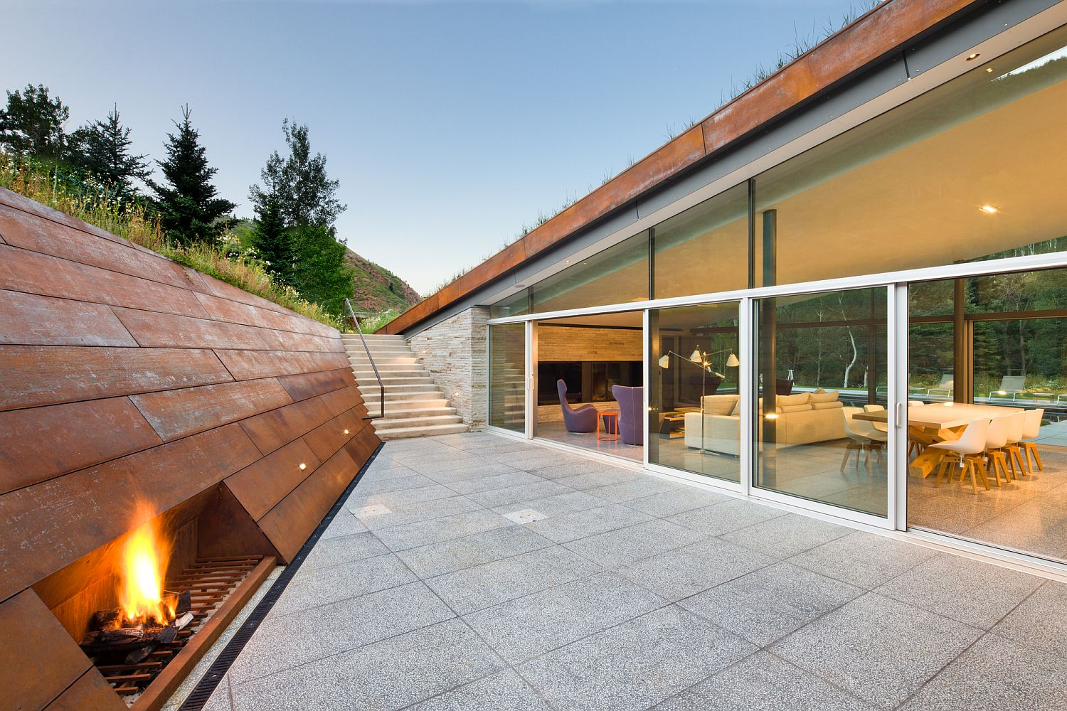 Corten clad wall for the sunken lounge inside the mountain home with green roof
