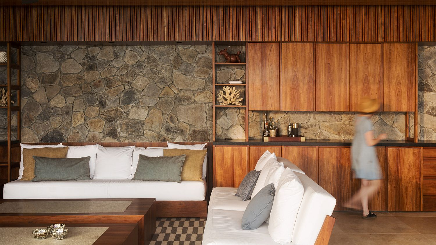 Stone and wood open living area that flows into the deck