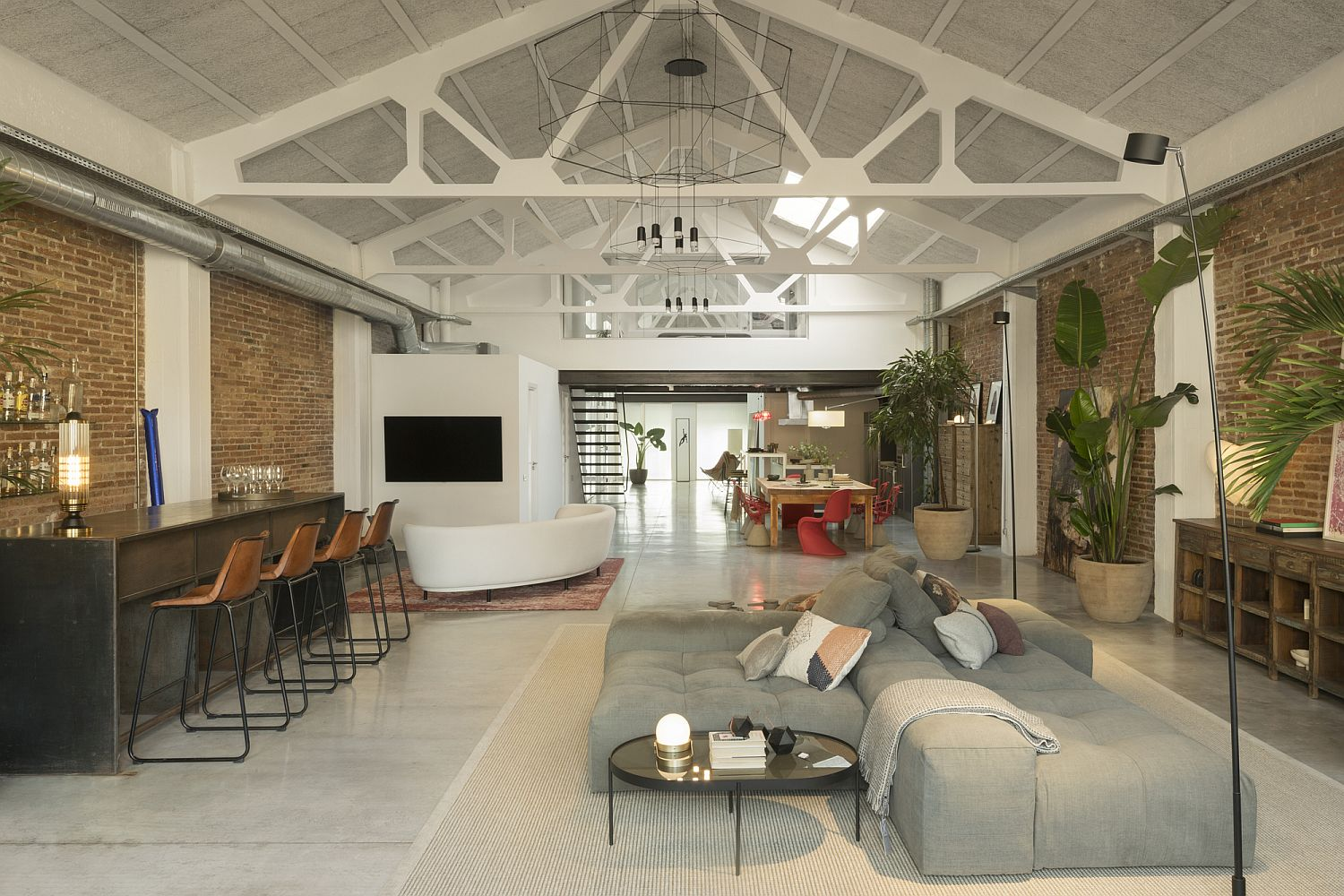 Delightful vaulted ceiling in white adds contemporary appeal to the industrial loft
