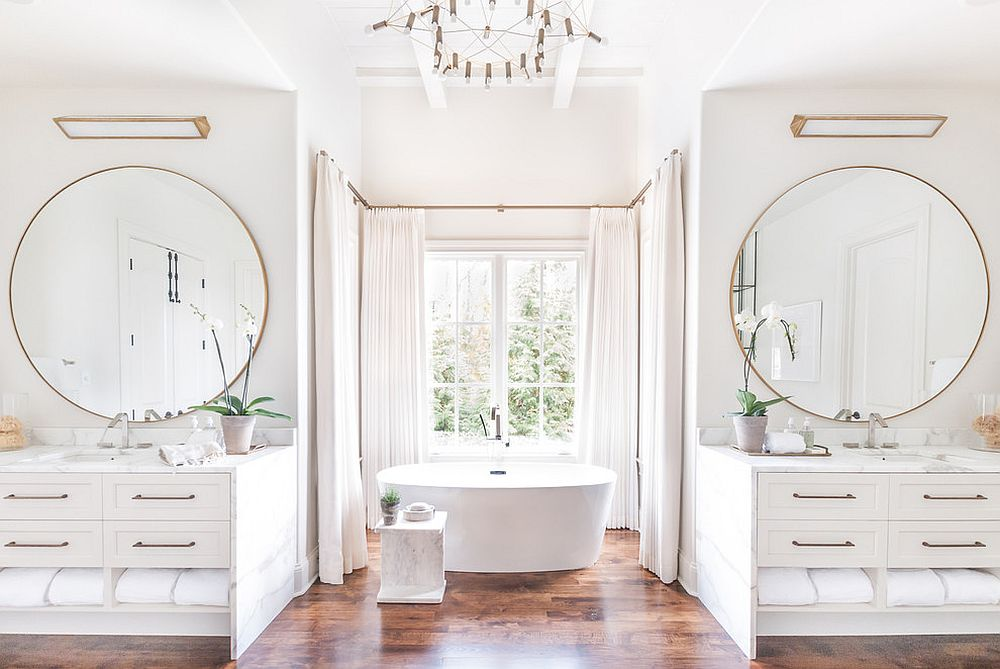 Gorgeous white bathroom with twin vanities, round mirrors and metallic accents