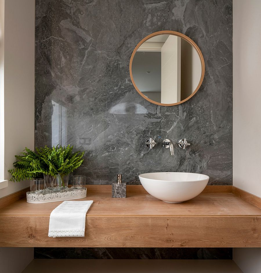 Slim floating vanity in wood with accent wall in stone