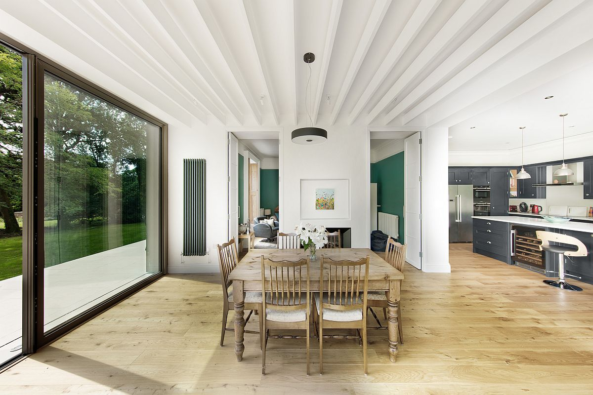 White and wood dining area of the house with sliding glass doors connecting it to the deck outside