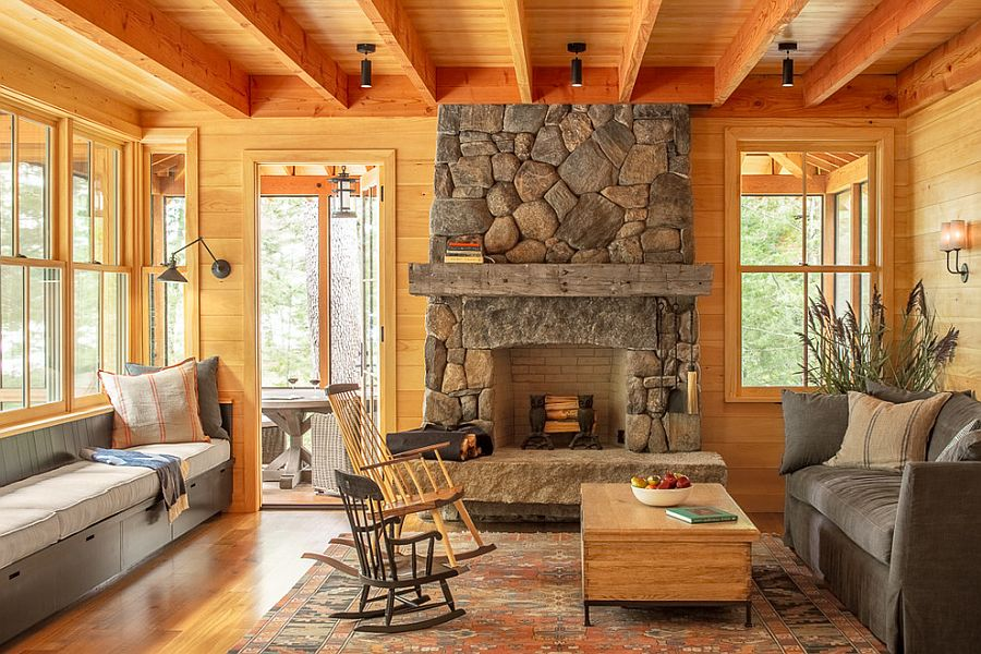 Wood-clad living room with comy benches and a stone fireplace