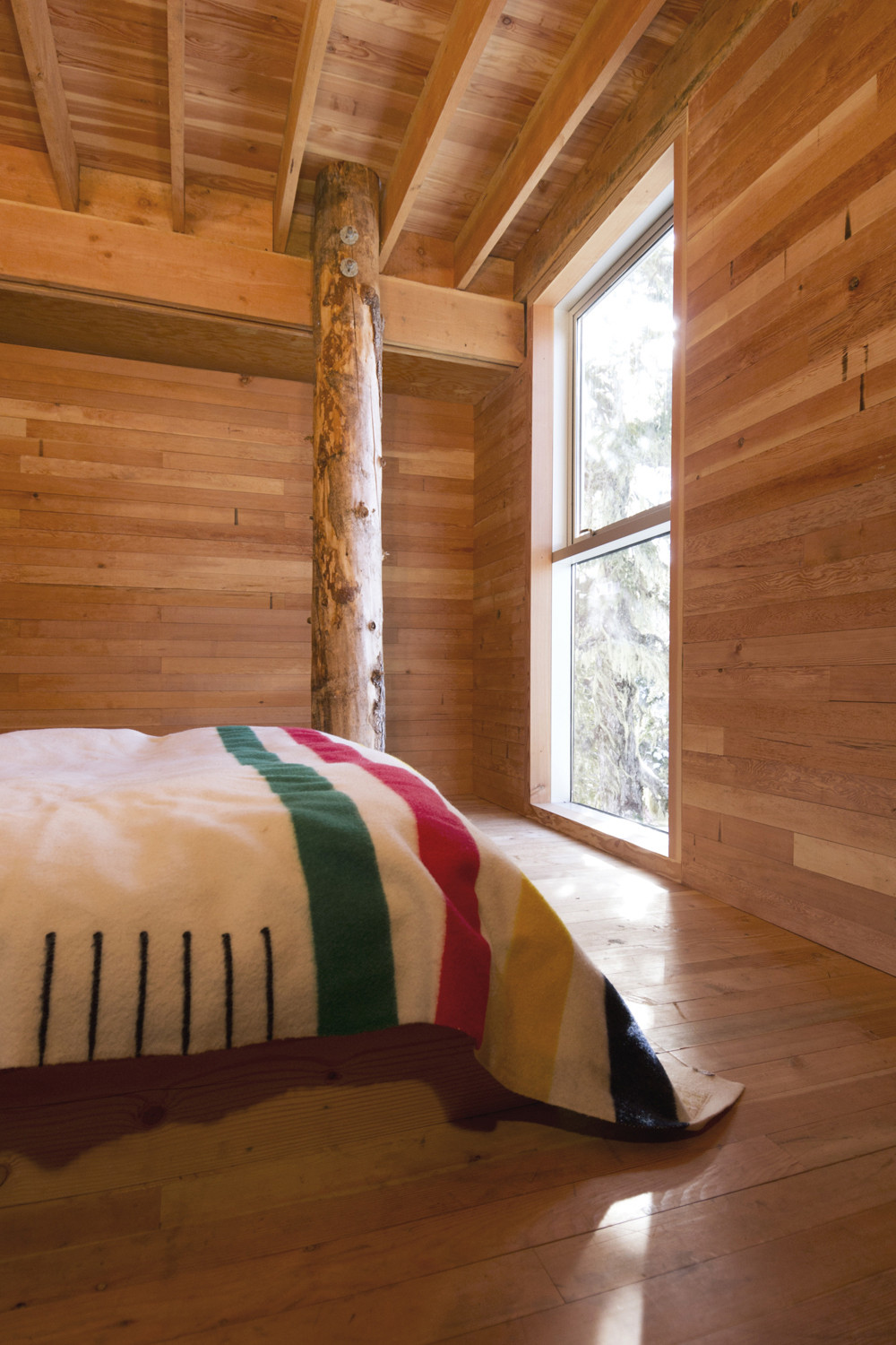 Bedroom of the cabin with a view of the snowy slopes above