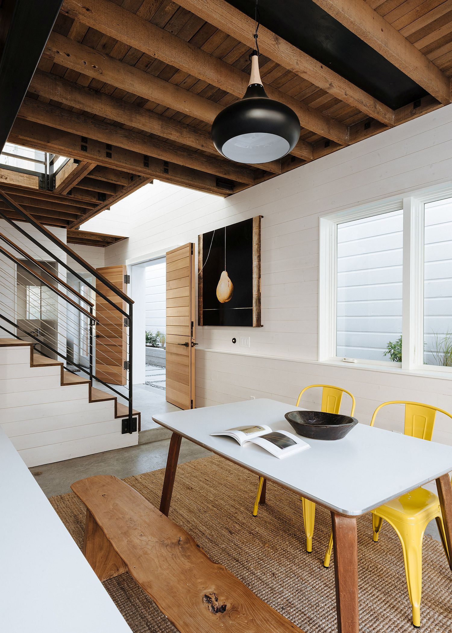 Stylish chairs in yellow add pops of color to the dining space in white and wood