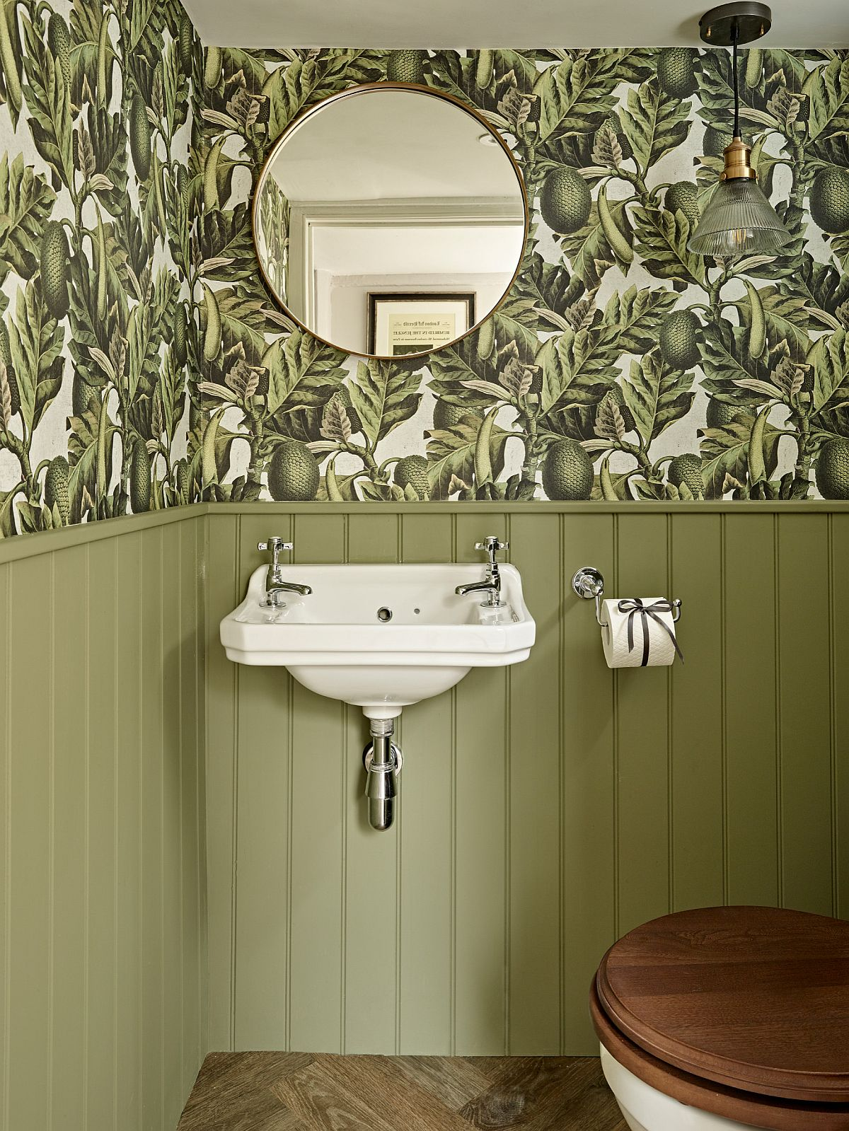 Both wallpaper and light green wall add color and class to the small farmhouse powder room with wall-mounted sink