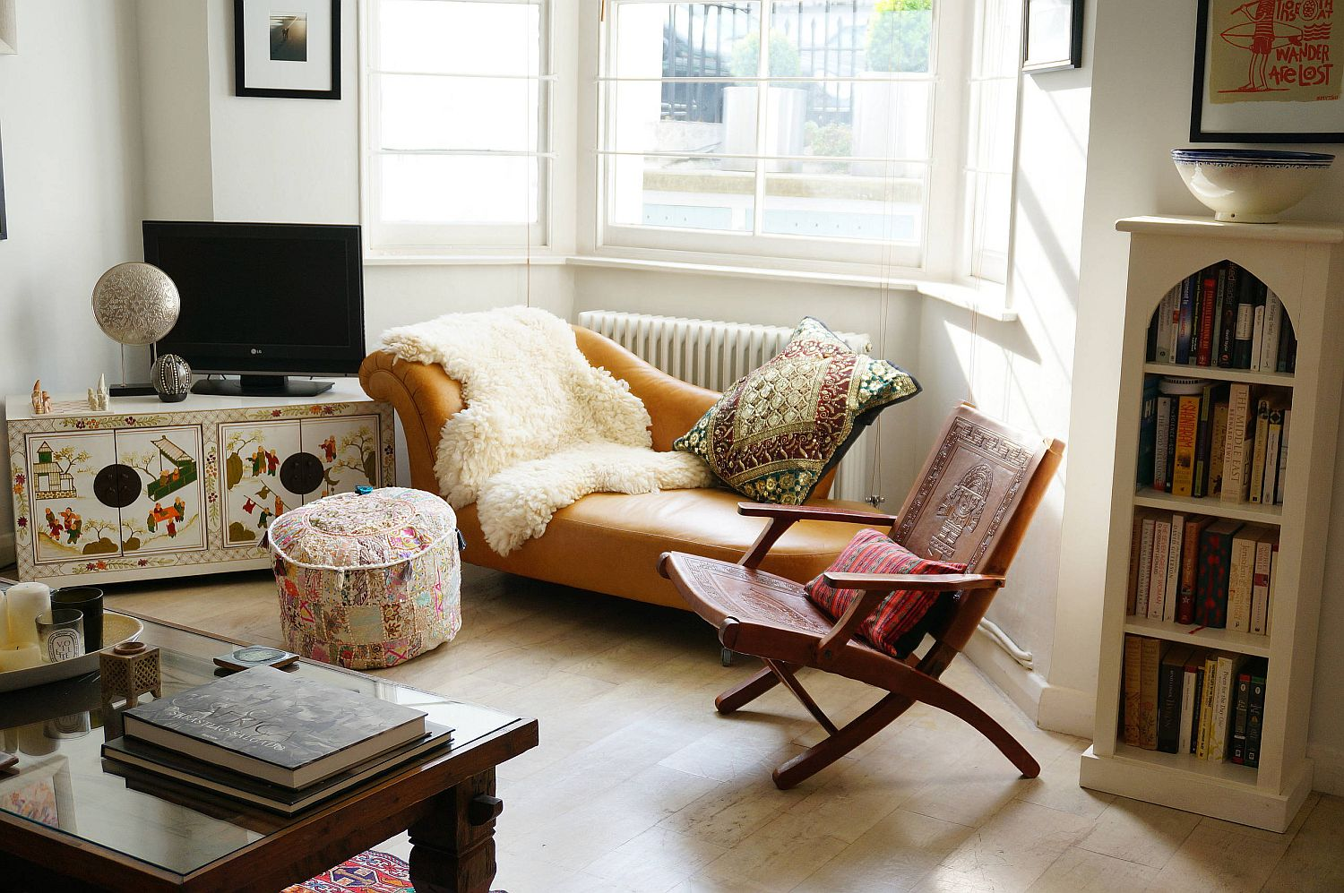 Classic chaise lounge, TV stand with pattern, ottoman and fluffy throw bring boho magic to this chic living space