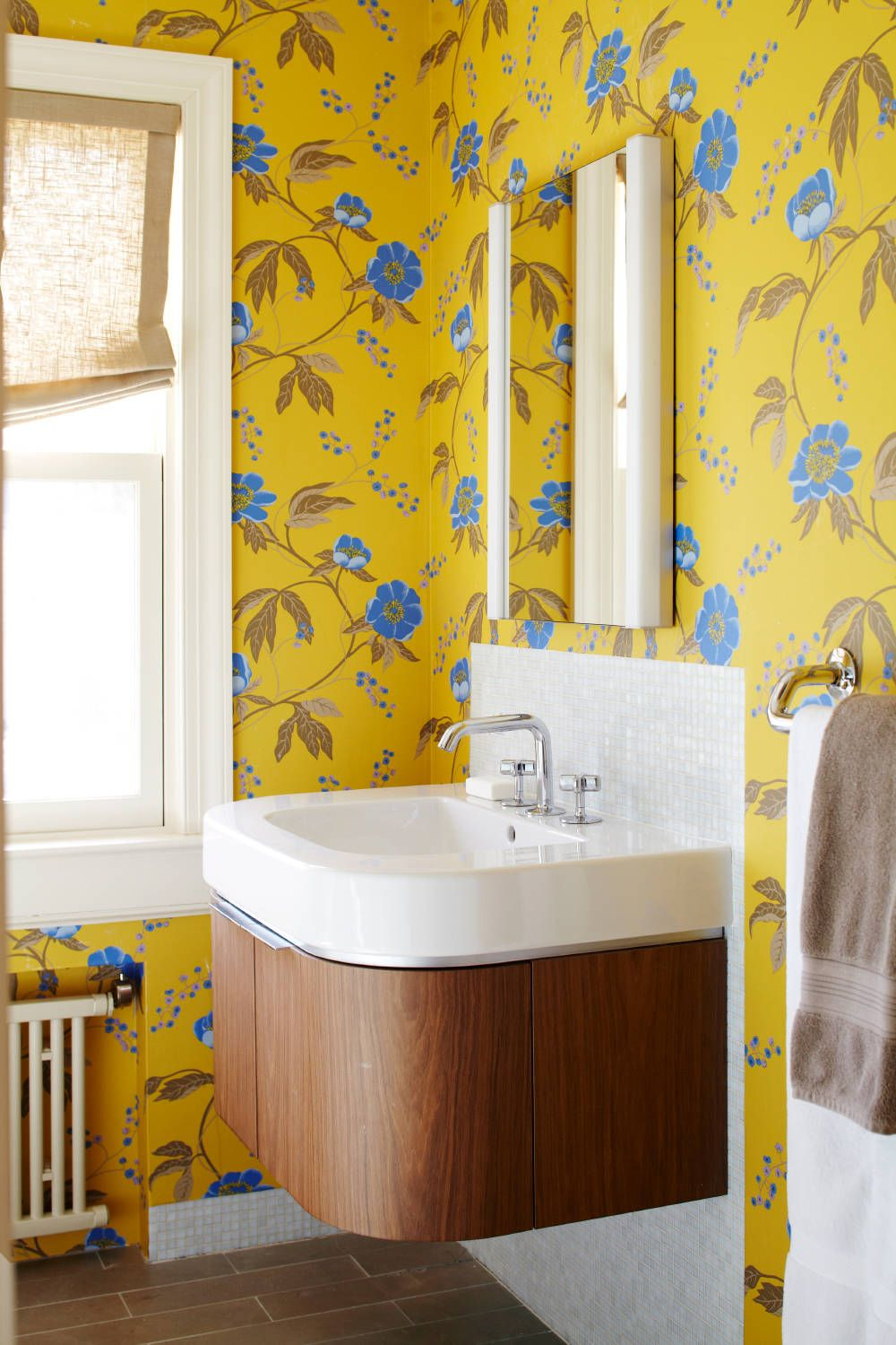 Eye-catching yellow wallpaper with bright blue pops inside the powder room